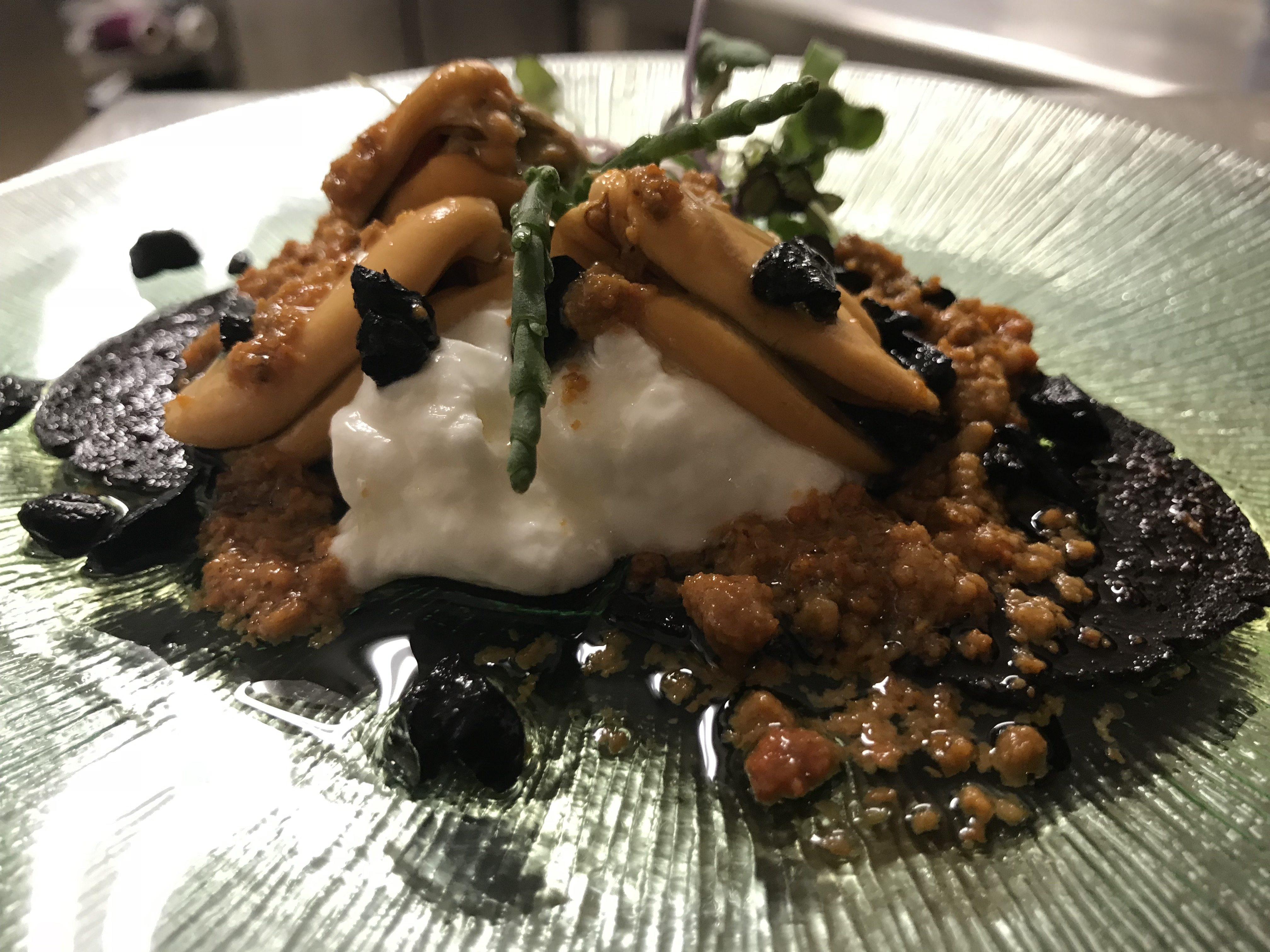 Mejillón sobre pan de ajo negro y vinagreta de oricios